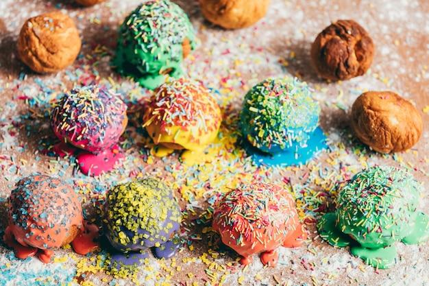Beignets saupoudrés colorés sur un comptoir sale.