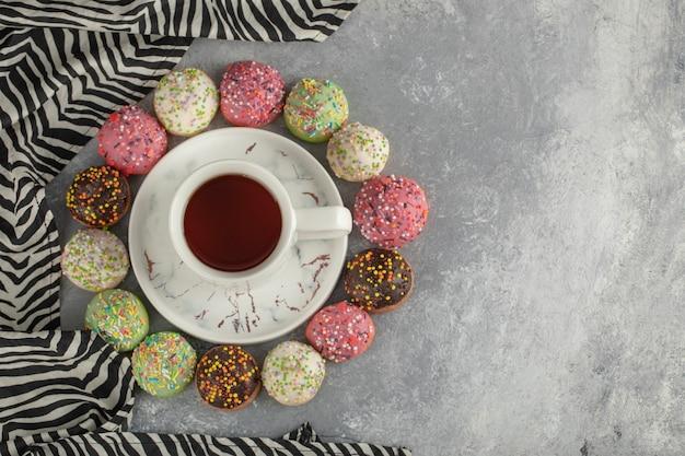 Beignets sucrés colorés avec une tasse de thé.