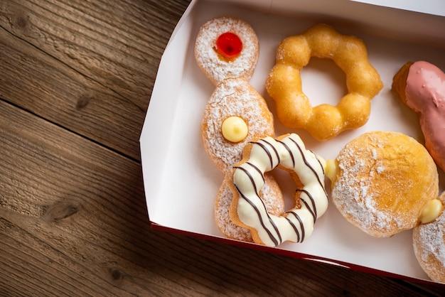 Beignets sucrés dans une boîte à beignets en papier collation dessert, différents types de beignets