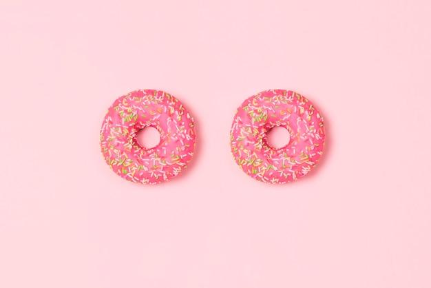 Beignets sucrés sur fond rose pastel vue de dessus à plat concept alimentaire