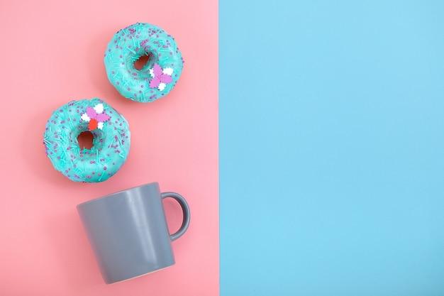 Beignets sucrés rose et bleu avec une tasse de café