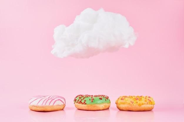 Beignets sucrés avec saupoudrage et lait sous un petit nuage sur fond rose. divers beignets décorés comme concept d'un délicieux petit-déjeuner frais.