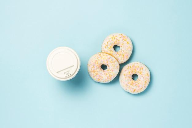 Beignets sucrés savoureux frais et une tasse de papier de café ou de thé sur un fond bleu. concept de restauration rapide, boulangerie, petit déjeuner ,. le minimalisme. mise à plat, vue de dessus.