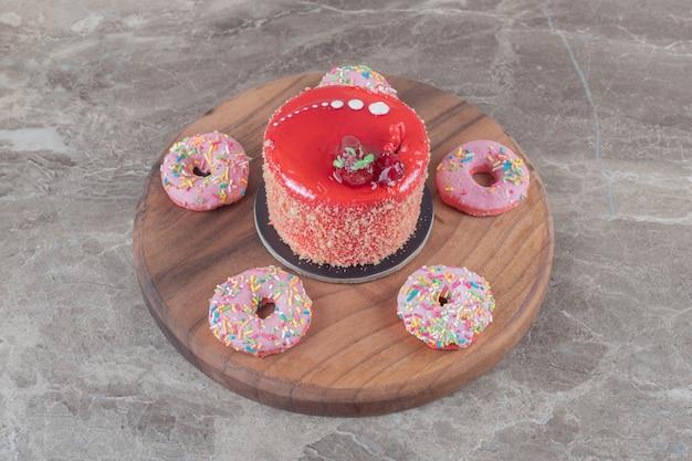 Beignets de la taille d'une collation autour d'un gâteau garni de sirop de fraise sur une planche sur une surface en marbre