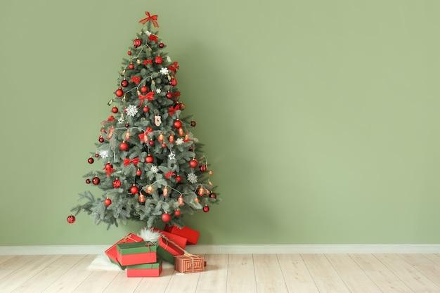 Bel arbre de noël décoré sur mur vert