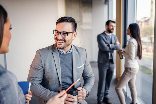 Bel architecte caucasien sympathique souriant tenant thermos avec café et parler avec son collègue. ils prennent tous une pause dans leur travail acharné.