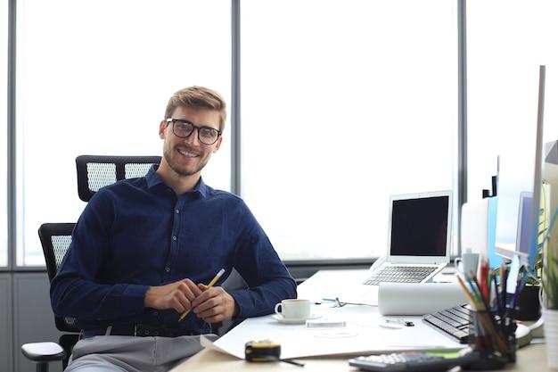 Bel architecte masculin regardant la caméra et souriant alors qu'il était assis au bureau.