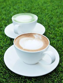 Bel art de café au lait chaud dans une tasse blanche sur fond d'herbe verte