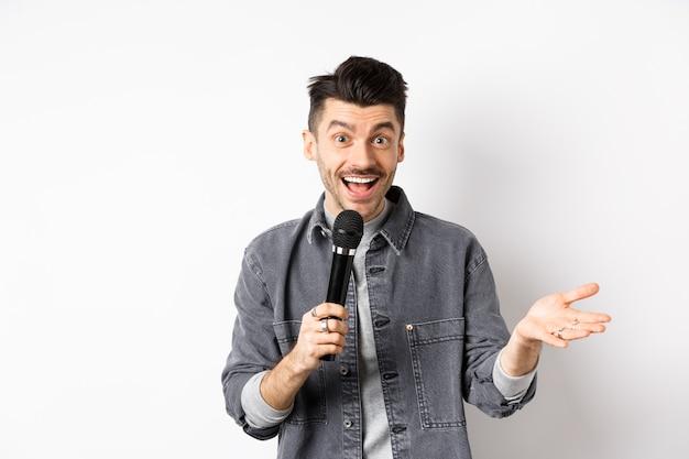 Bel artiste souriant parlant au micro, faisant des gestes et effectuant, faisant un discours avec microphone, debout sur fond blanc.