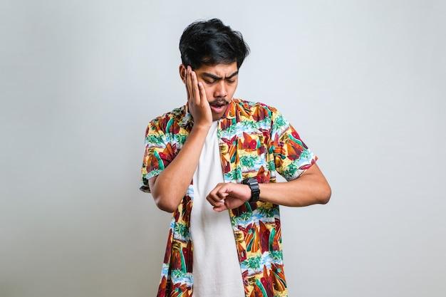 Bel asiatique portant des vêtements décontractés regardant l'heure de la montre inquiet, craignant d'être en retard sur fond blanc