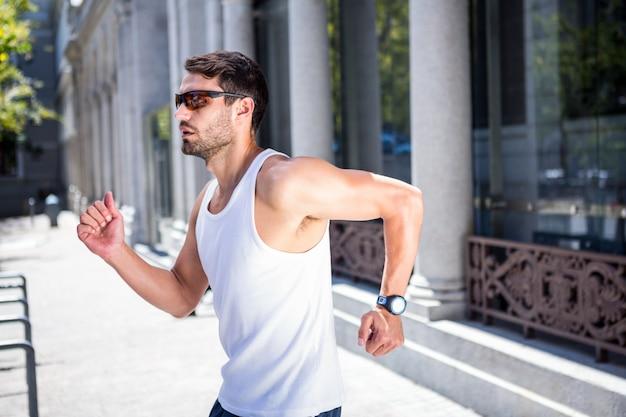 Bel athlète avec des lunettes de soleil jogging