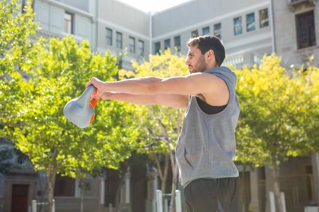 Bel athlète soulevant la cloche de la bouilloire