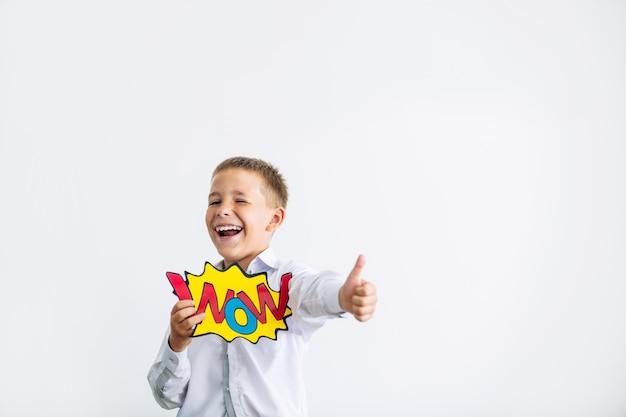 Bel écolier enfant en classe à l'école sur fond blanc avec wow du portrait heureux comique avec concept