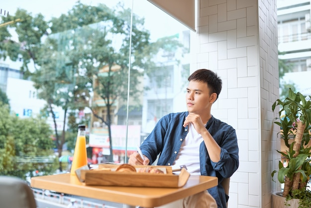 Bel écrivain indépendant masculin créant un article publicitaire pour une société de marketing notant les meilleures idées dans le journal avant de terminer la publication pour la sortie travaillant dur le matin assis dans un café