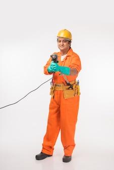Bel électricien ou ingénieur asiatique indien en action avec un chapeau de sécurité jaune isolé
