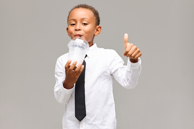 Bel élève mâle adorable à la peau foncée portant une chemise blanche et une cravate noire faisant le geste du pouce en l'air tout en sirotant un milk-shake sain pendant la pause déjeuner à l'école, ayant un regard joyeux
