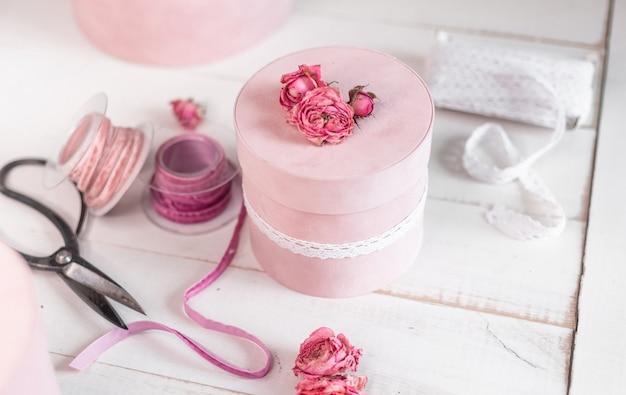 Le bel emballage cadeau rond rose est décoré de roses rétrécies