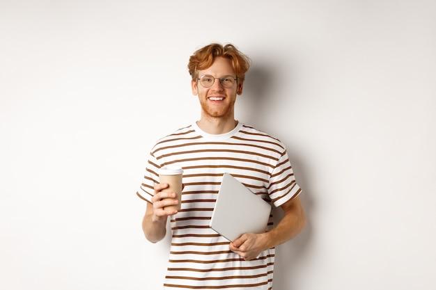 Bel employé de sexe masculin rousse dans des verres ayant une pause, boire du café et tenant un ordinateur portable, debout sur fond blanc