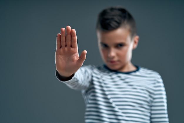 Bel enfant agacé par une mauvaise attitude faisant un panneau d'arrêt avec la main, disant non, exprimant la sécurité, la défense ou la restriction isolée sur fond gris.