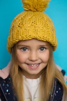Bel enfant dans un bonnet jaune sur fond bleu, sourire