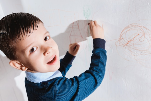 Le bel enfant dessine sur le mur avec des crayons colorés