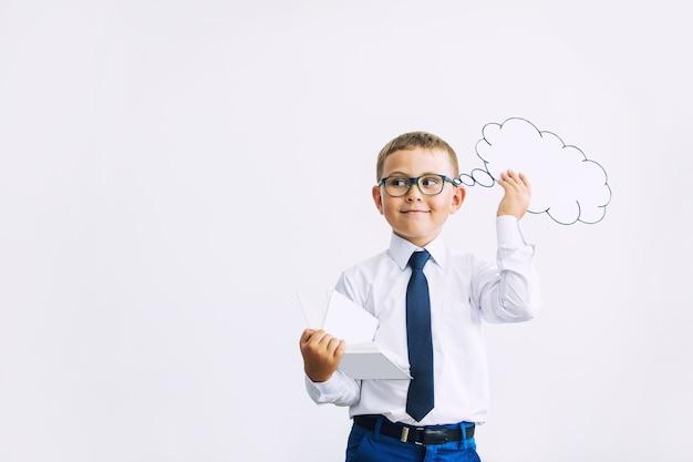 Bel enfant étudiant dans la classe à l'école sur un fond blanc avec le nuage de pensées