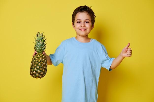 Bel enfant garçon tenant un ananas et montrant le pouce vers le haut