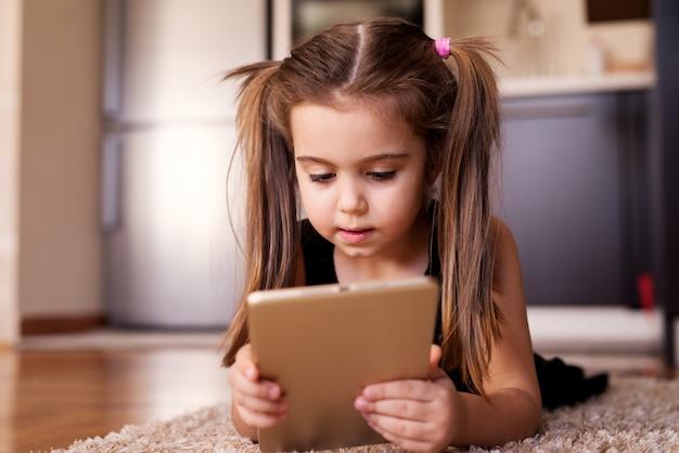 Bel enfant petite fille avec des queues de cheval jouant avec une tablette en position couchée sur le sol.