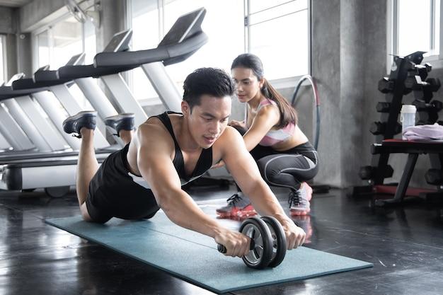Bel entraînement asiatique par roue ab sur l'exercice de tapis de yoga avec femme sont des formateurs au gymnase.