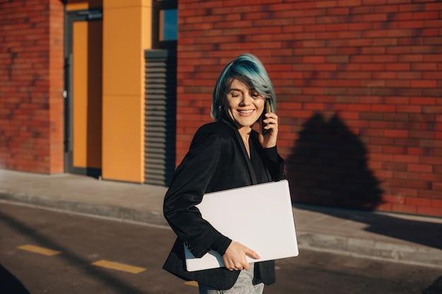 Bel entrepreneur caucasien aux cheveux bleus, parler au téléphone et marcher avec un ordinateur portable