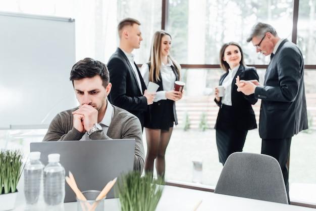 Bel entrepreneur avec ordinateur portable assis dans un bureau moderne et pensant, tandis que ses collègues font une pause avec un café.