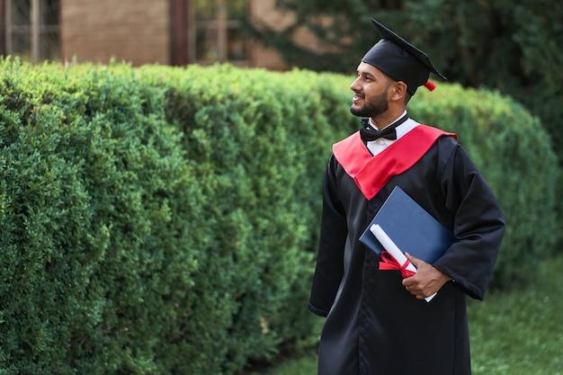 Bel étudiant indien célébrant l'obtention du diplôme sur le campus universitaire avec diplôme en robe.