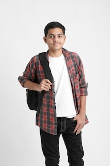 Bel étudiant avec sac à dos debout sur un mur blanc
