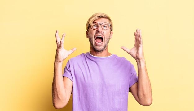 Bel homme adulte blond criant furieusement, se sentant stressé et ennuyé avec les mains en l'air disant pourquoi moi