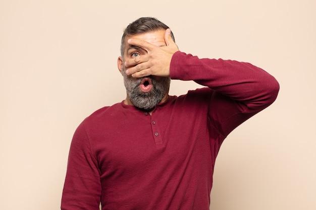 Bel homme adulte à choqué, effrayé ou terrifié, couvrant le visage avec la main et furtivement entre les doigts
