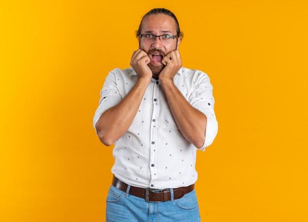 Bel homme adulte concerné portant des lunettes gardant les mains sur le visage regardant la caméra avec la bouche ouverte isolée sur un mur orange avec espace de copie