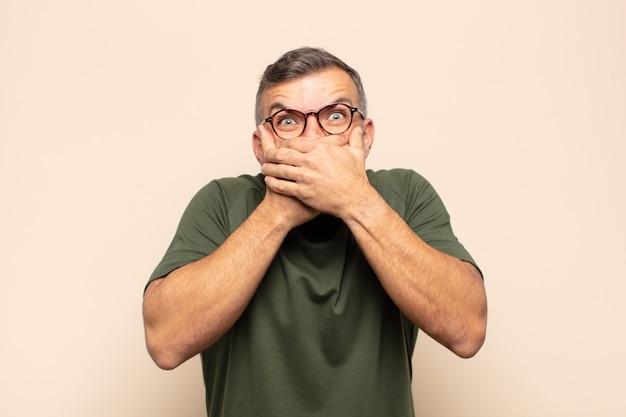 Bel homme adulte couvrant la bouche avec les mains avec une expression choquée et surprise, gardant un secret ou disant oups