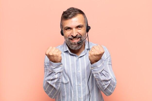 Bel homme adulte criant triomphalement, riant et se sentant heureux et excité tout en célébrant le succès
