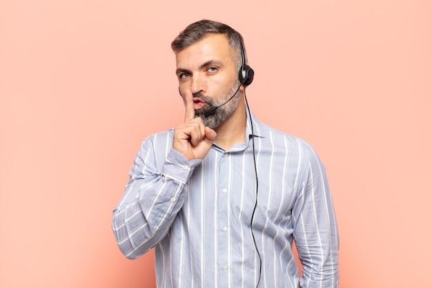 Bel homme adulte demandant silence et silence, faisant des gestes avec le doigt devant la bouche, disant chut ou gardant un secret