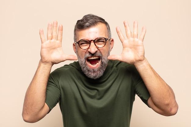 Bel homme adulte hurlant de panique ou de colère, choqué, terrifié ou furieux, avec les mains à côté de la tête
