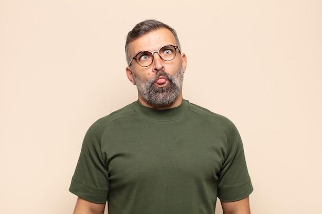 Bel homme adulte à la recherche de maladroit et drôle avec une expression idiote aux yeux croisés, plaisantant et s'amusant