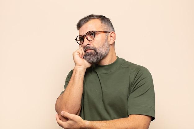 Bel homme adulte avec un regard concentré, se demandant avec une expression douteuse, levant les yeux et sur le côté