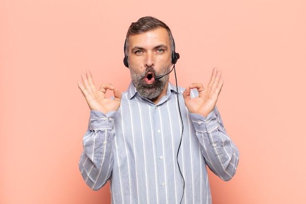 Bel homme adulte se sentant choqué, étonné et surpris, montrant son approbation faisant signe d'accord avec les deux mains