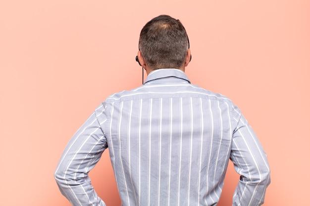 Bel homme adulte se sentant confus ou plein ou des doutes et des questions, se demandant, avec les mains sur les hanches, vue arrière