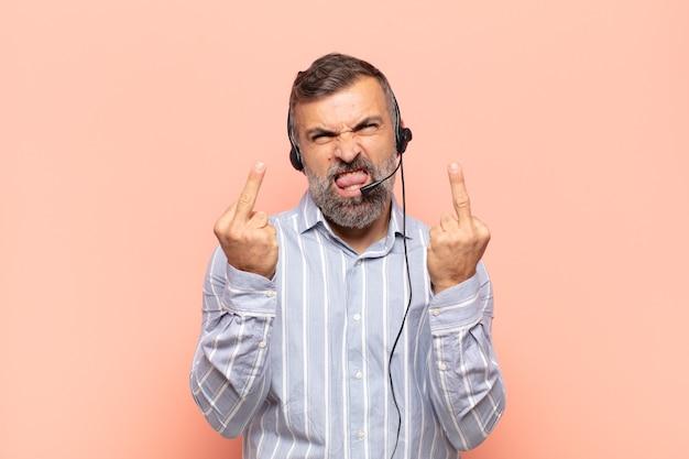 Bel homme adulte se sentant provocateur, agressif et obscène, retournant le majeur, avec une attitude rebelle