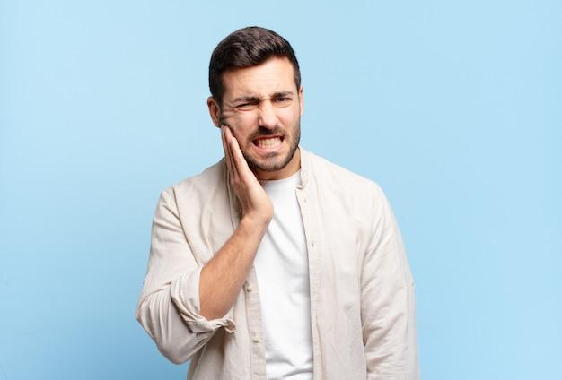 Bel homme adulte tenant la joue et souffrant de maux de dents douloureux, se sentir malade, misérable et malheureux, à la recherche d'un dentiste