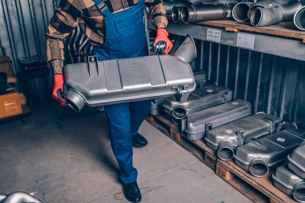 Bel homme adulte travaillant dans un entrepôt de pièces détachées pour voitures et camions.