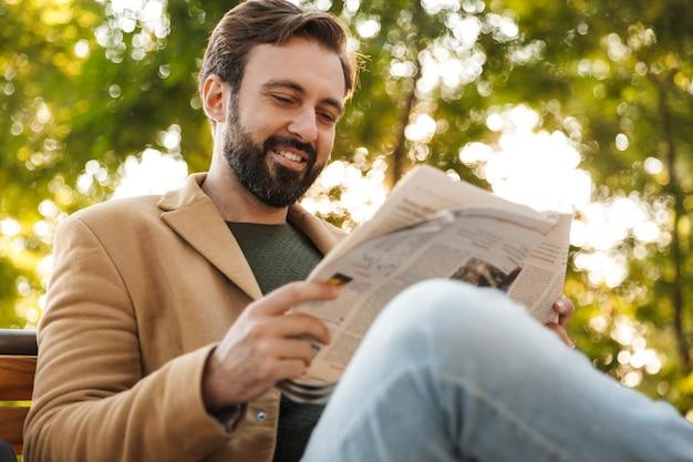 Bel homme adulte en veste souriant et lisant le journal assis sur un banc dans le parc