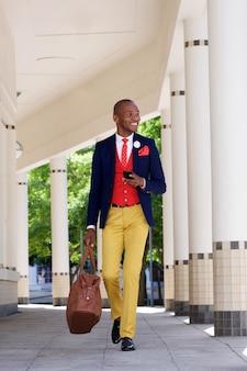 Bel homme d'affaires africain marchant avec téléphone portable