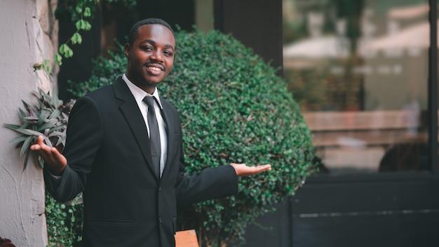 Le bel homme d'affaires africain se tient sur un geste de bienvenue. style 16: 9